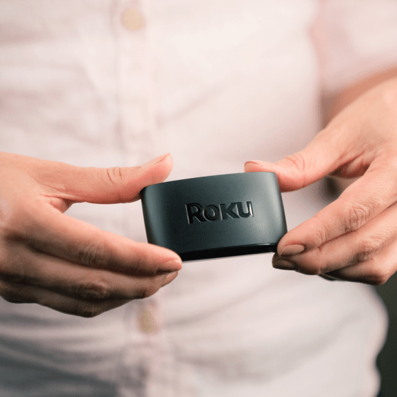 Person holding a Roku Express+ to show its small size