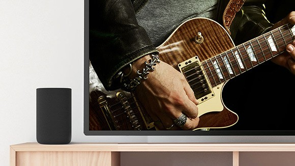 One Roku TV Wireless Speaker next to a TV playing rock music