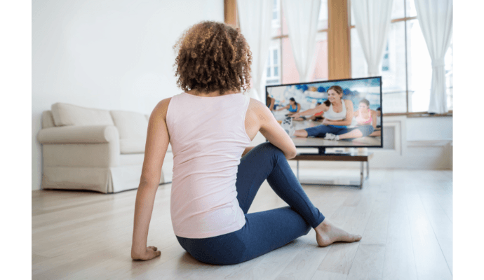 woman exercising along with a tv